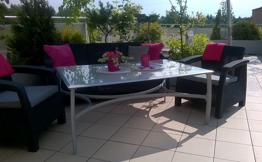 Sofa trzyosobowa i dwa fotele uzupełnione szklanym stołem
