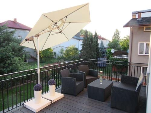 Duży taras w bloku osłonięty parasolem.