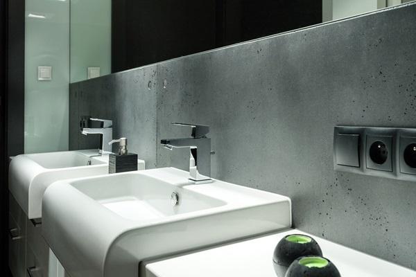 Płyty betonowe na ścianę zamontowane nad umywalkami.
