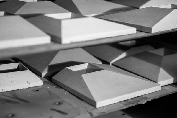 Dekory betonowe SLABB schną na półkach w manufakturze.