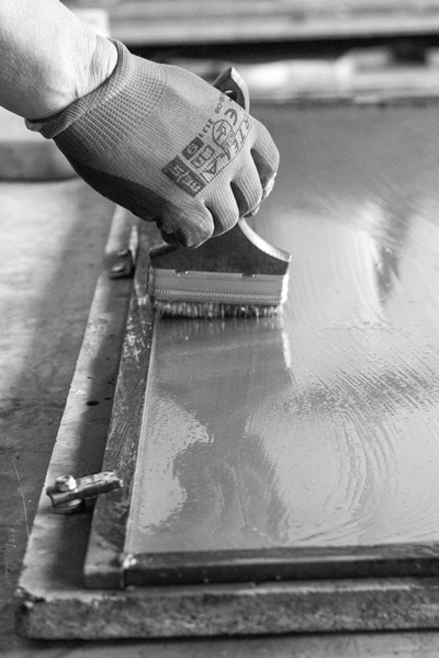 Smarowanie płyt wodą - jeden z etapów przygotowania produktów.