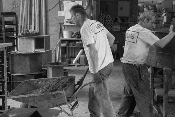 Pracownicy manufaktury SLABB transportują gotowy beton do warsztatów.