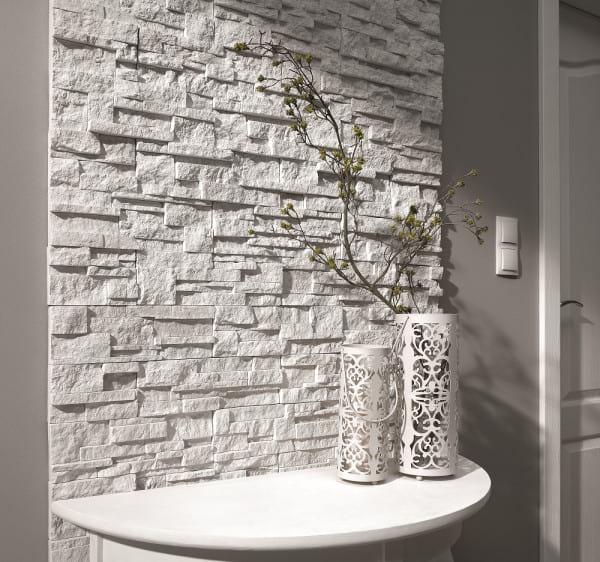 Kamień na ścianie w przedpokoju Alaska Vanilla Incana Stone połączony z ozdobnym stolikiem.