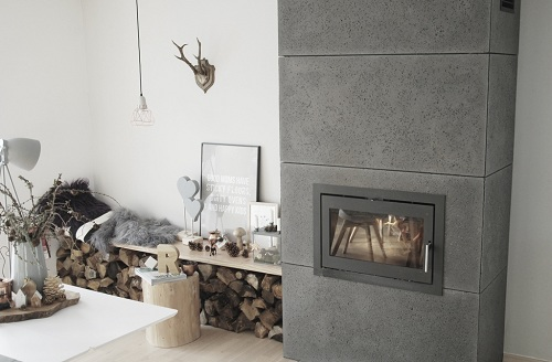 Wnętrze w stylu skandynawskim z kominkiem wykończonym betonem architektonicznym.