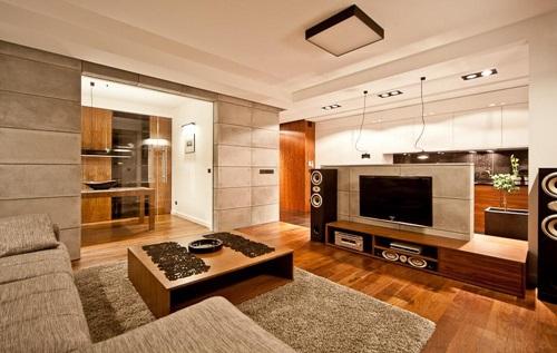 Kącik telewizyjny w salonie ozdobionym betonem architektonicznym.