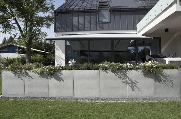 Beton architektoniczny w aranżacji tarasu - betonowe donice SLABB wyznaczające granicę między tarasem a ogrodem.