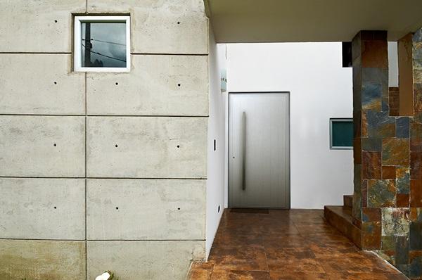 Beton architektoniczny zestawiony na wykończeniu elewacji z kamieniem dekoracyjnym do ogrodu.