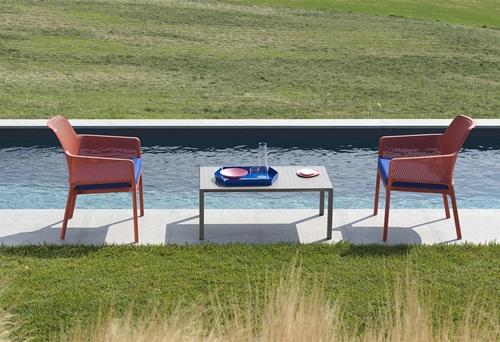 Włoskie meble ogrodowe Nardi ustawione tuż nad dużym ogrodowym basenem.