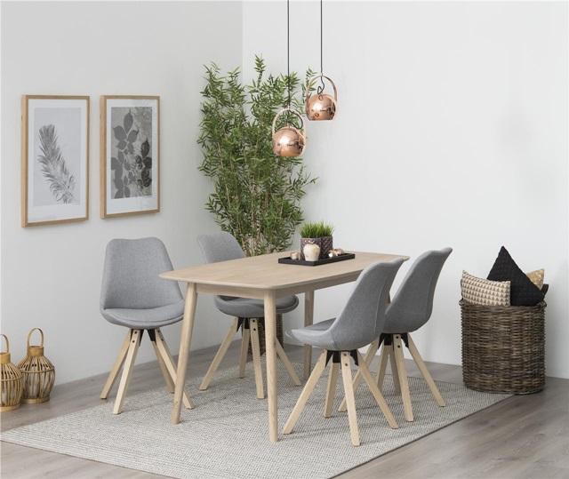Styl skandynawski w małym mieszkaniu - stół z krzesłami uzupełniony o modne miedziane dodatki.