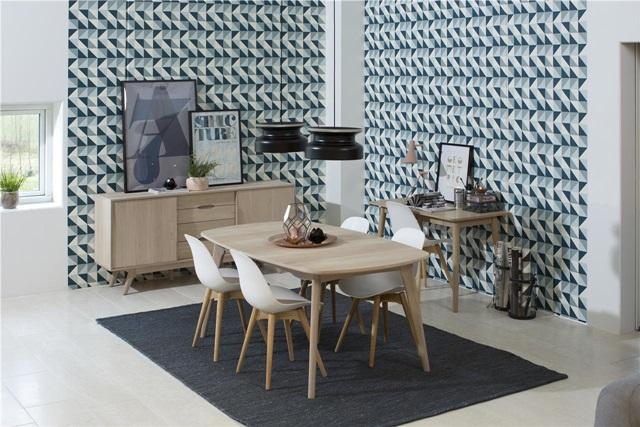 Jasny drewniany stół z krzesłami styl skandynawski z ciekawą geometryczną tapetą.