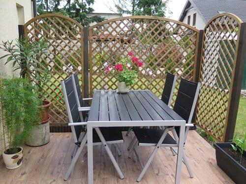 Dobre meble ogrodowe aluminiowe na osłoniętym od wiatru tarasie.