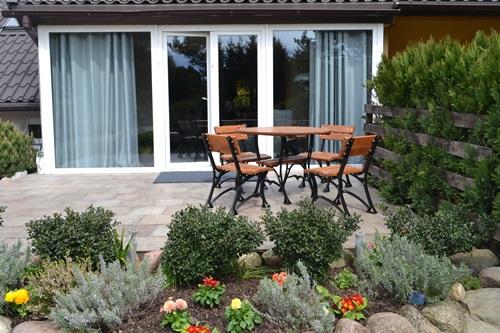 Dobre meble ogrodowe drewniane Restor na tarasie otoczonym elegancką rabatą.
