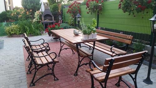 Dobre meble ogrodowe drewniane ozdobione kwiatami.