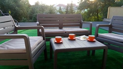 Dobre meble ogrodowe plastikowe Delano Set podczas podwieczorku.
