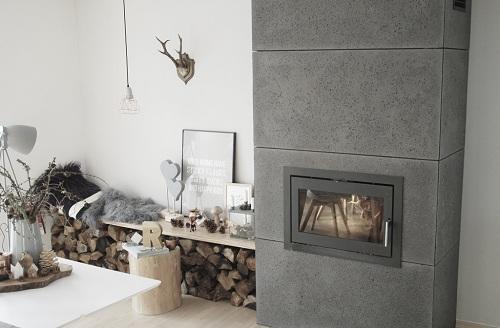 Wnętrze w stylu skandynawskim z kominkiem wykończonym betonem architektonicznym