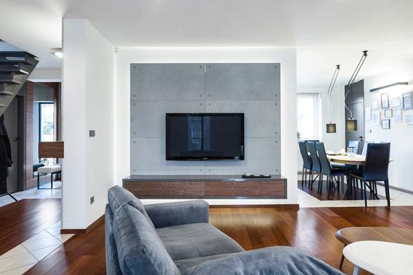 Betonowe płyty dekoracyjne tworzące tło dla telewizora