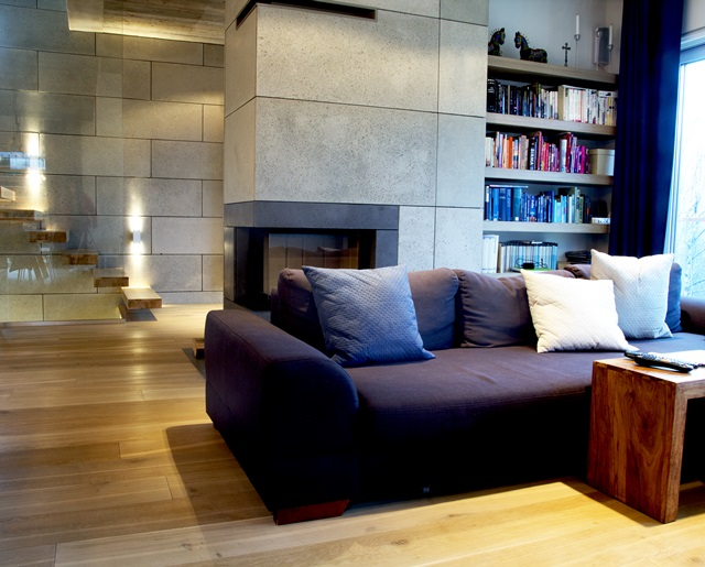 Ściana z betonu w salonie zestawiona z kolorową sofą