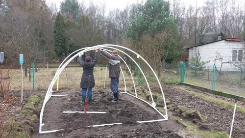 Dziadek i babcia montują pałąki tunelu z poprzeczkami.