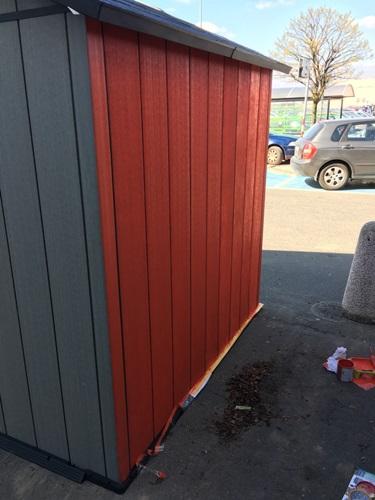 Końcowy etap malowania domków Keter Oakland - usuwanie taśmy malarskiej.