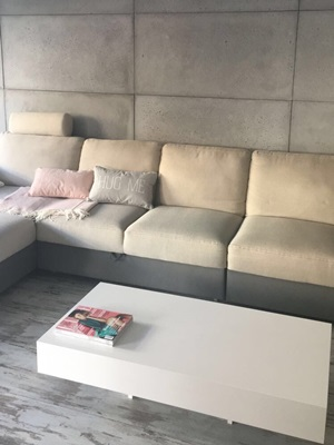 Salon ze stolikiem Pixel X i ścianą ozdobioną betonem architektonicznym