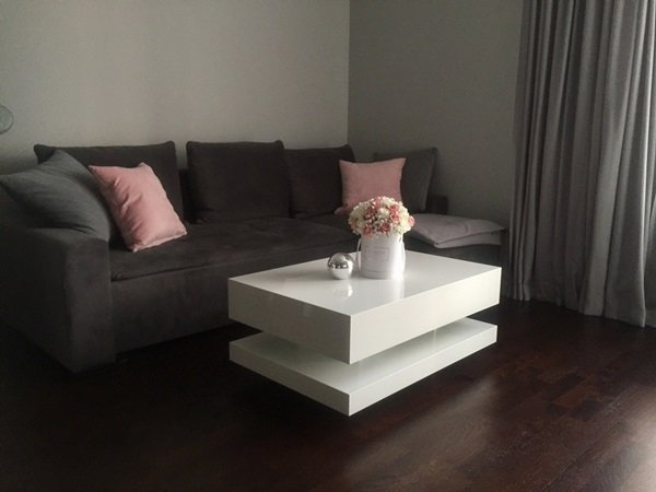 Przytulny salon pani Natalii z białym stolikiem kawowym na wysoki połysk